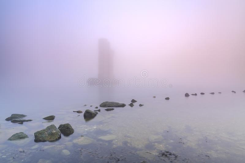 Pillar of a storm surge barrier in fog during sunset. One of the remaining pillars of the storm surge barrier standing in water during a heavy dense foggy winter stock image