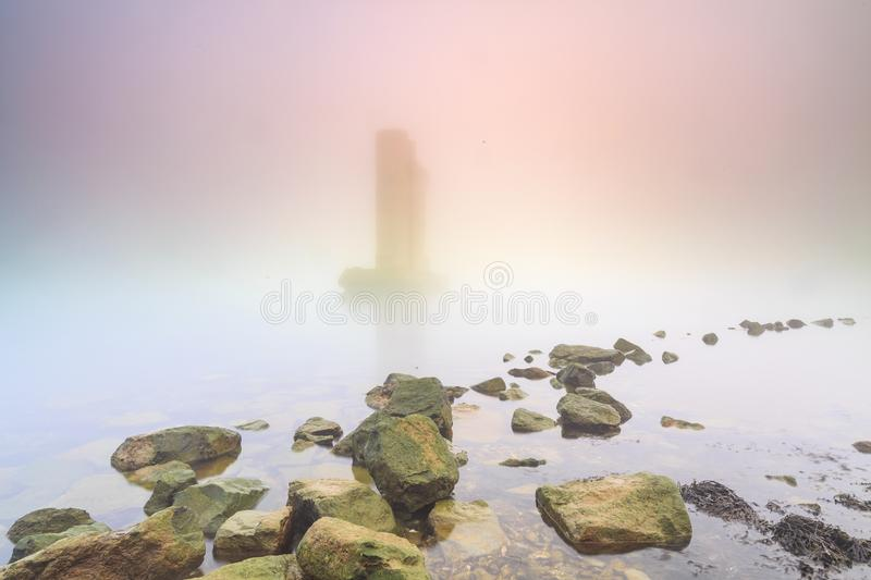 Pillar of a storm surge barrier in fog during sunset. One of the remaining pillars of the storm surge barrier standing in water during a heavy dense foggy winter stock photos