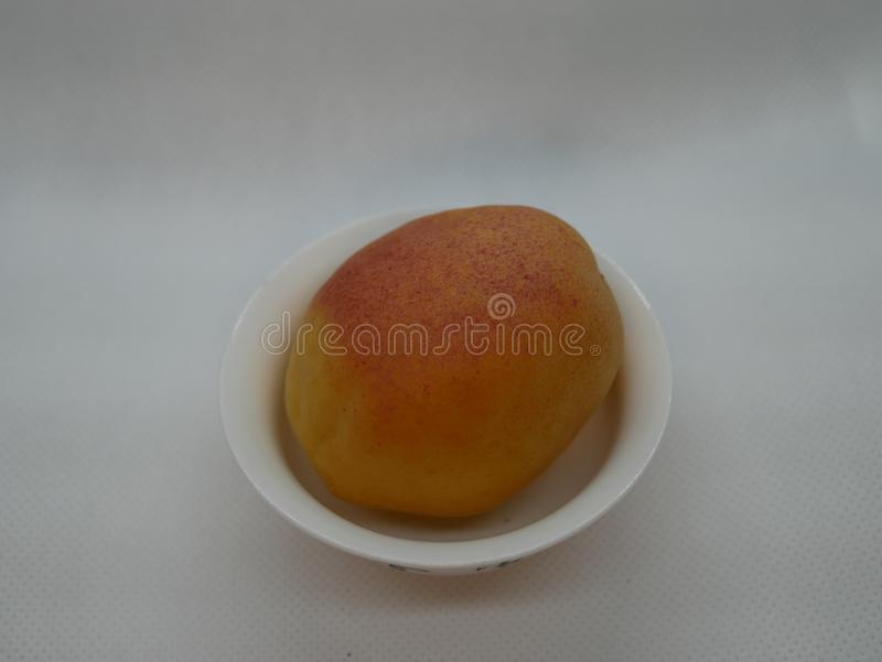 One ripe apricot in a small white porcelain plate on a white background. Natural vitamin. Healthy food. vegetarian food. One ripe apricot in a small white stock photography