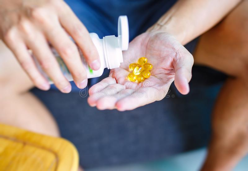 Close up photo of one round yellow pill in hand. Man takes medicines with glass of water. Daily norm of vitamins, effective drugs, royalty free stock photos