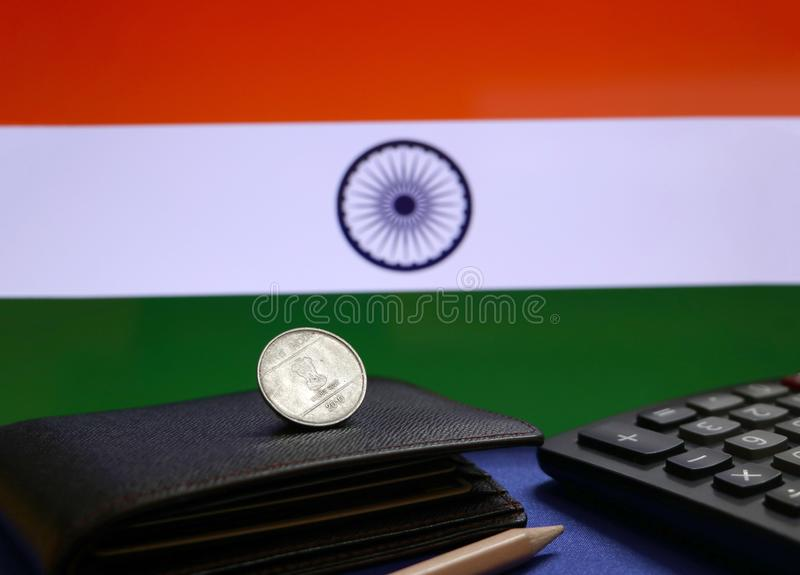 One Rupee coin of India on the black wallet, pencil and calculator with Indian flag background. Concept of finance or currency royalty free stock images