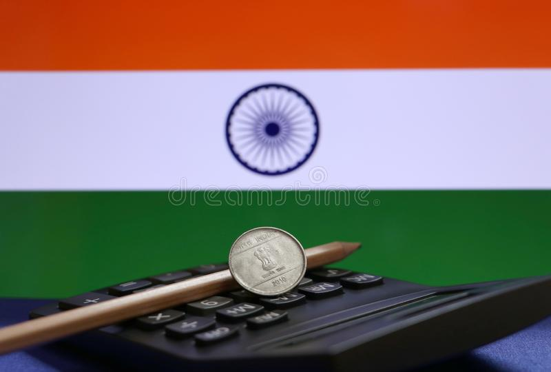 One Rupee coin of India on the calculator and pencil with Indian flag background. Concept of finance or currency royalty free stock photos