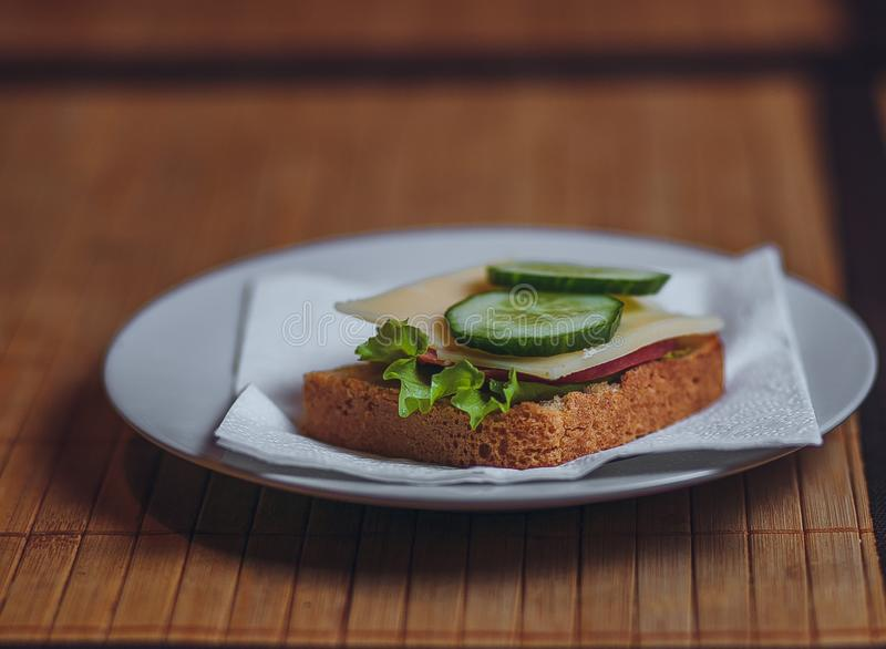 One sandwich with sausage cheese and cucumber is on a white plate stock photos