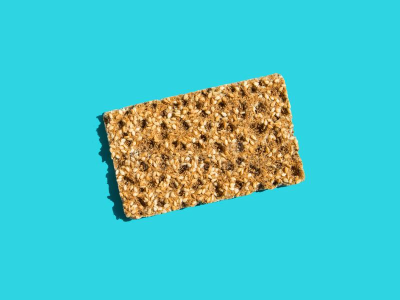 One scandinavian rye whole grain crispbread with sesame seeds on solid blue background. Harsh shadows hard light. Trendy. Minimalist pop art style. Balanced royalty free stock photo