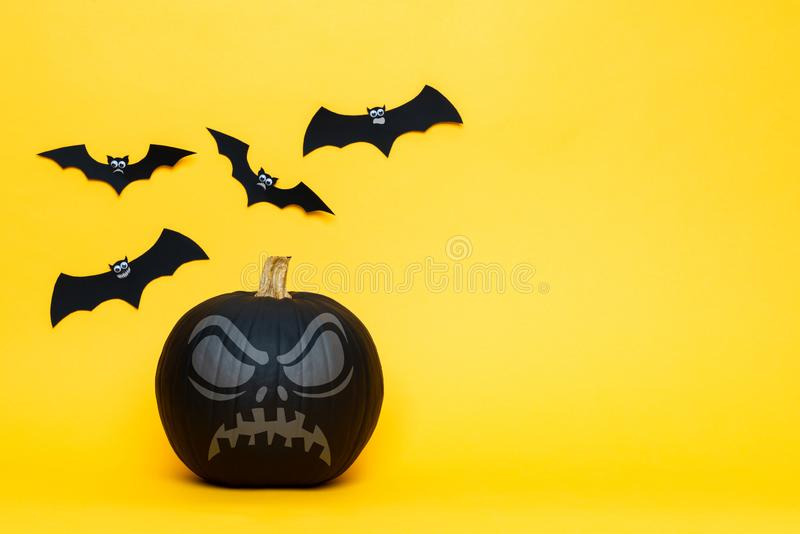 One scary black Jack o Lantern and flying paper bats over yellow background. Halloween background with copy space. One scary black Jack o Lantern and flying stock images