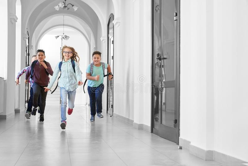 One school girl running first and other boys after. royalty free stock photos