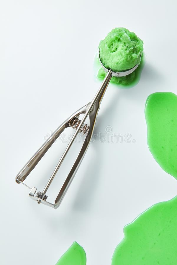 One scoop of pistachio ice cream on a gray background with splashes and a copy of space. Top view royalty free stock photos