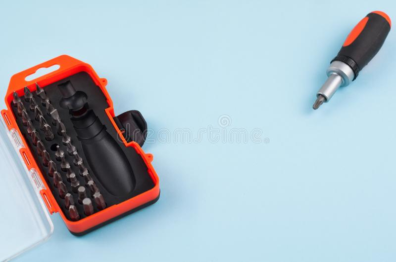 One screwdriver with handle of black and orange color near set of metal bits in box on blue background. With copy space stock photography