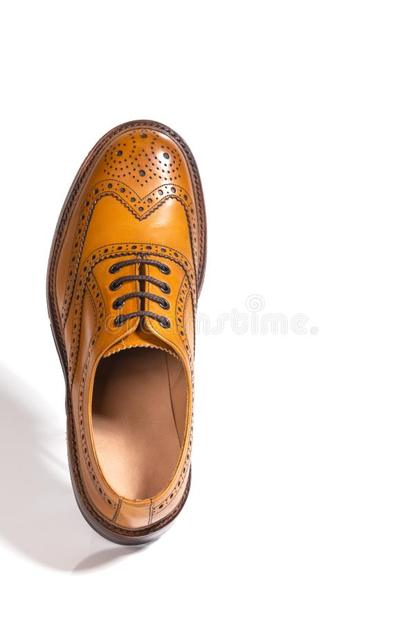 One Separate Male Tan Brogue Oxford Shoe. Isolated Over White Ba. Closeup of One Separate Male Tan Brogue Oxford Shoe. Isolated Over White Background. Vertical stock photo
