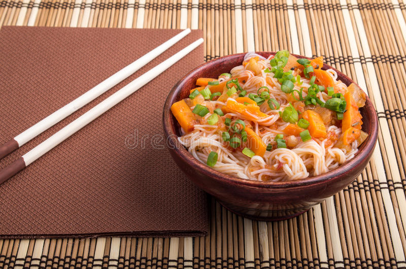 One serving of rice vermicelli hu-teu with vegetables. One serving of rice vermicelli hu-teu with vegetable carrot sauce in a small brown wooden bowl on a royalty free stock photo