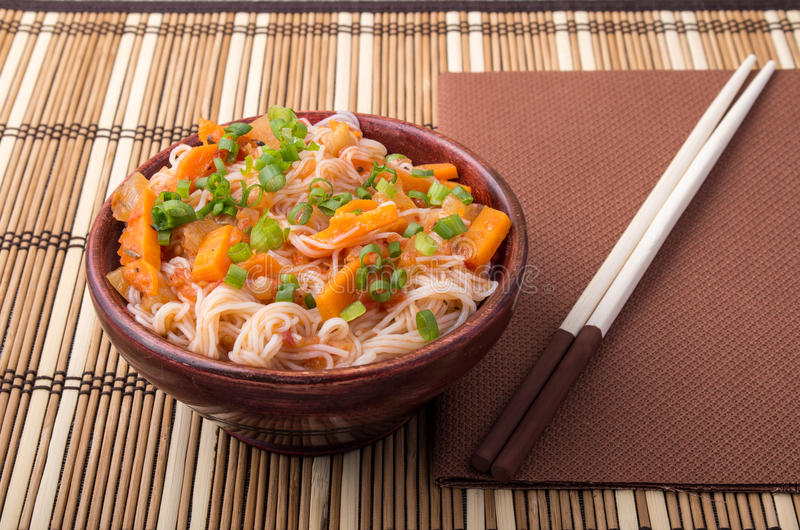 One serving of rice vermicelli hu-teu with vegetables. One serving of rice vermicelli hu-teu with vegetable carrot sauce in a small brown wooden bowl on a stock image