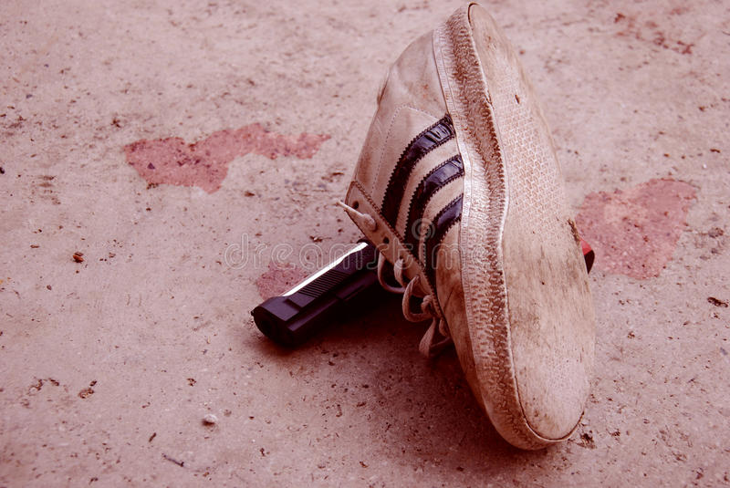 One shoes/sneakers and a gun in the street with bloodstain in background stock image