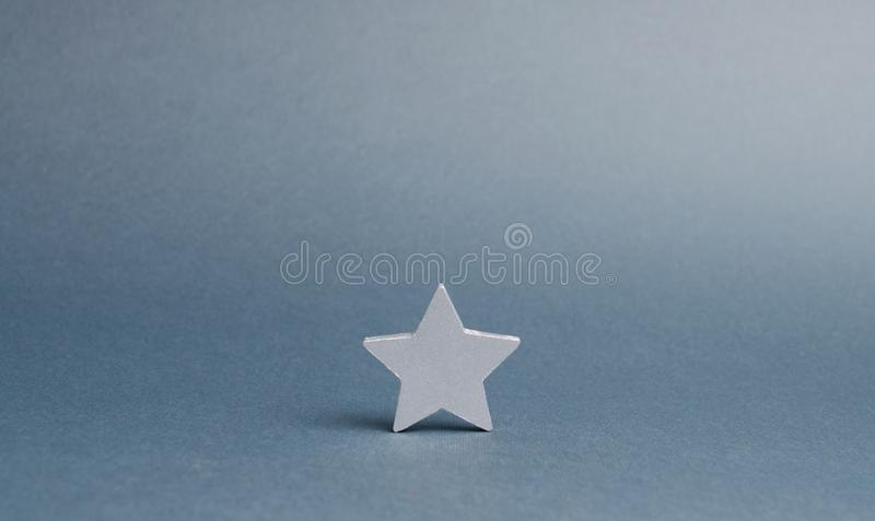 One silver star on a gray background. The concept began the way of business to success, the first steps. The growth of reputation. And quality. Single star stock photography