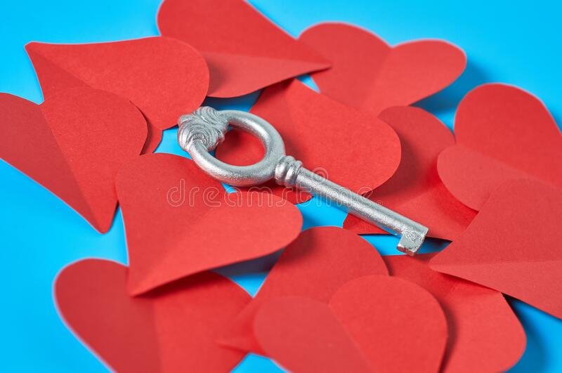 One silver vintage key on heap of red paper hearts lies on blue countertop. Concept of closed or opened love or Valentines day. Close-up royalty free stock photography