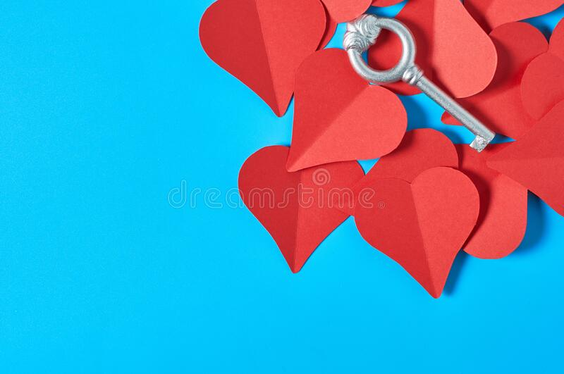 One silver vintage key on heap of red paper hearts lies on blue countertop. Concept of closed or opened love or Valentines day. Space for text. Top view. Flat royalty free stock image