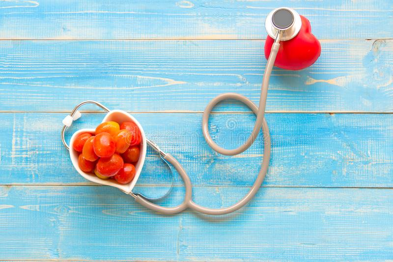 One single alone red heart love shape hand exercise ball with bandage MD medical doctor physician`s stethoscope blue wood backgrou stock image