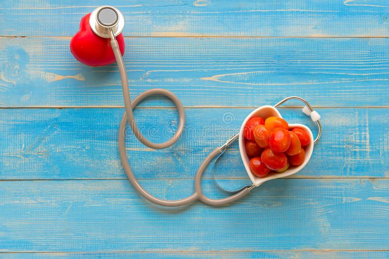 One single alone red heart love shape hand exercise ball with bandage MD medical doctor physician`s stethoscope stock photo