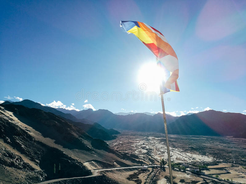 One single Buddhist prayer flag in six colors fluttering in mountain region against the sunlight stock image