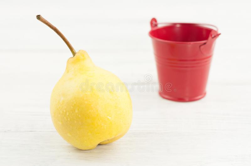 One single fresh yellow ripe whole pear and empty red metal bucket. On old rustic white wooden table stock images