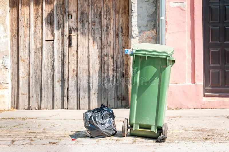 One single green garbage can and black plastic junk bag on the street in the city waiting for dumper truck to collect in front of stock images
