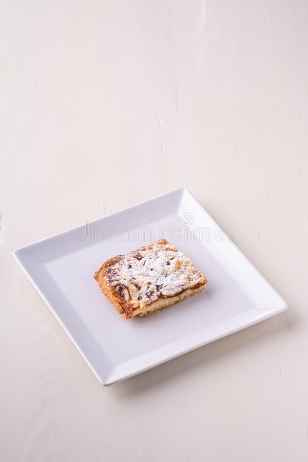 One single pieces of homemade cookies apricot jam powdered sugar in white square plate stock photos