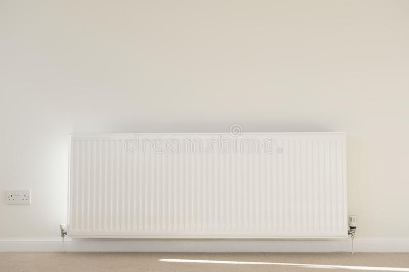 One single radiator single white in lounge neutral background carpet and wall for home heating royalty free stock images
