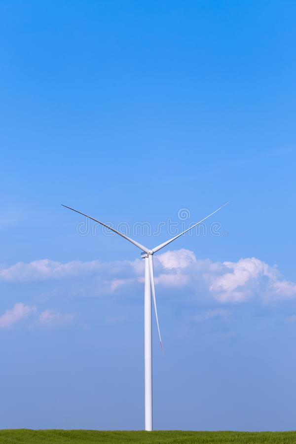 One single windmill turbine on green agricultural field with blue sky in background. Renewable energy wind turbine stock photo