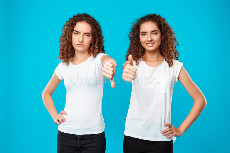 One of sisters twins showing dislike, another like over blue background. stock image