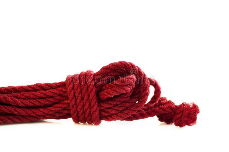 One skein of jute rope six millimeters for Japanese bondage and shibari, painted in red on a white background. Professionally knitted hank royalty free stock photography