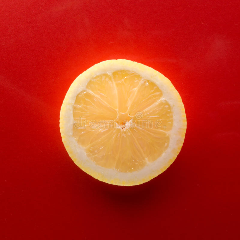One slice of lemon on red background, square shot royalty free stock photography