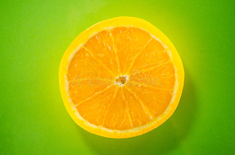 One slice of orange closeup on green background, horizontal shot stock photography