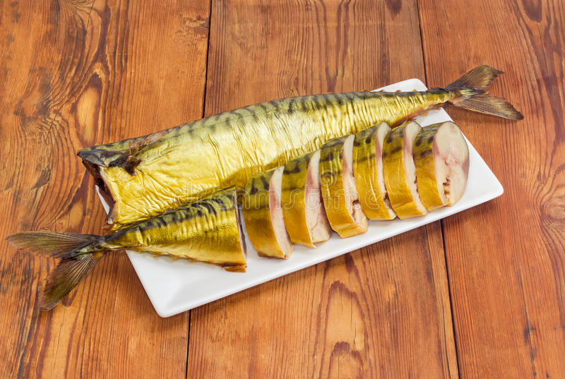 One sliced and one whole smoked Atlantic mackerel on dish stock photo