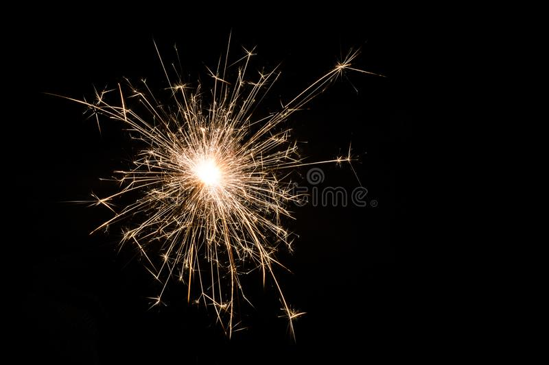 One small new year sparkler on black background royalty free stock photos
