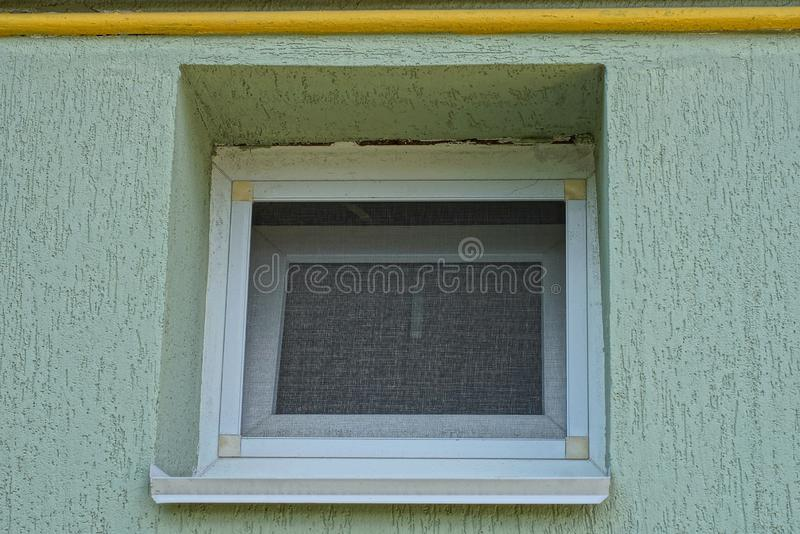 One small white square window on the gray wall royalty free stock image