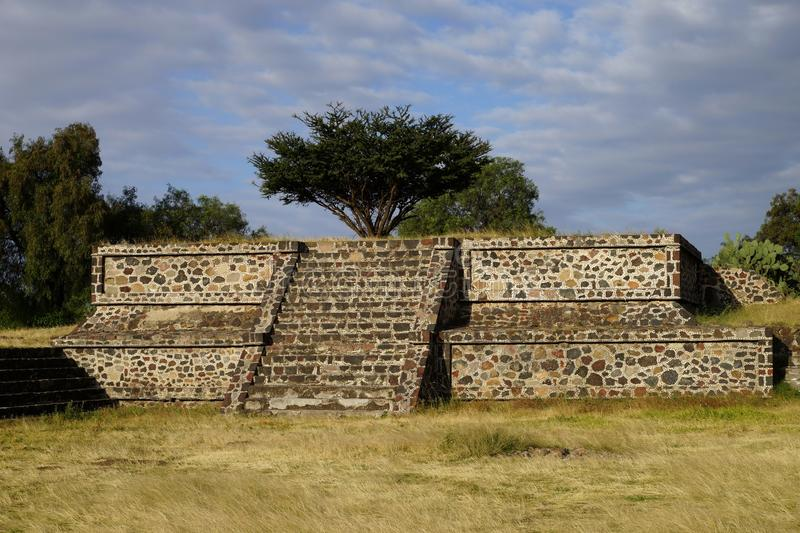 One of the smaller pyramids in Teotihuacan, Mexico. One of the smaller pyramids with a tree growing on the top in Teotihuacan, Mexico royalty free stock photo