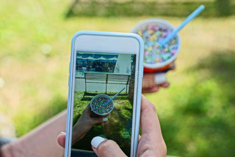 Smartphone in the hands of a girl doing a photo of a colored ice cream in a cup outside in the park royalty free stock image