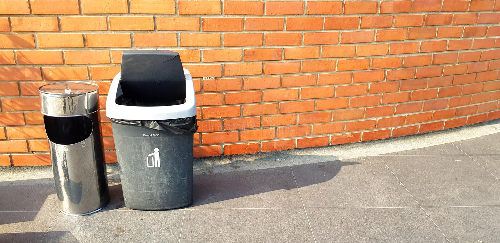 One stainless steel and Black plastic garbage putting on street with brown brick wall for people dumping trash, dross or refuse. And copy space - Cleaning area royalty free stock image