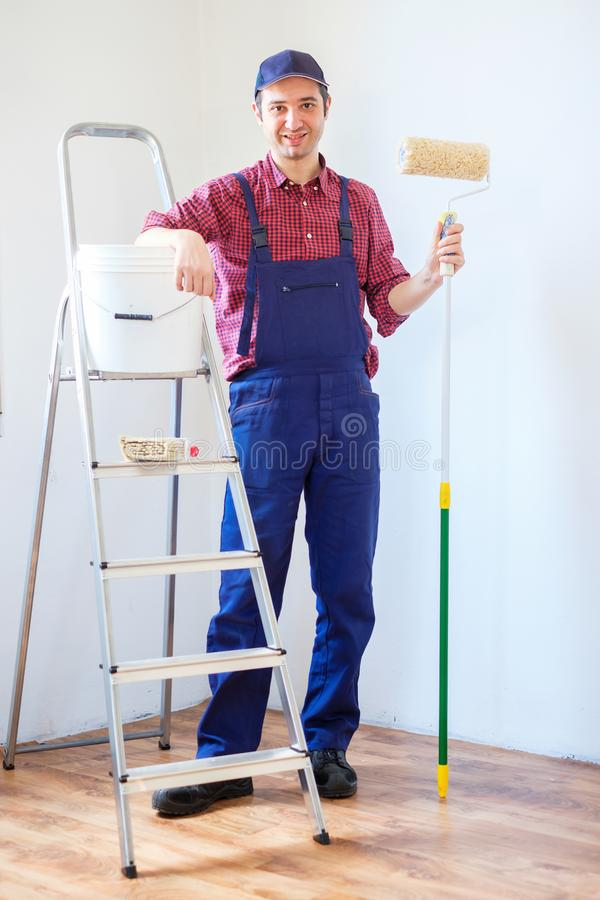 Painting the walls in the room using paint roller stock image
