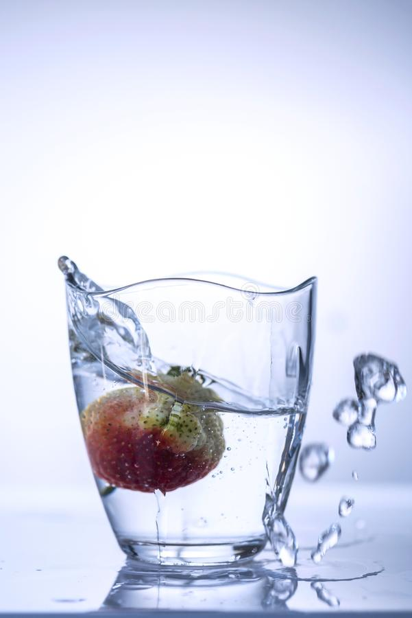 One strawberry splashing water from a glass on a white background, close up, abstract royalty free stock photography