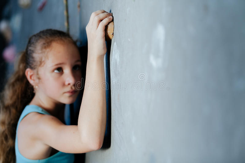 One teenager climbing a rock wall indoor. royalty free stock images