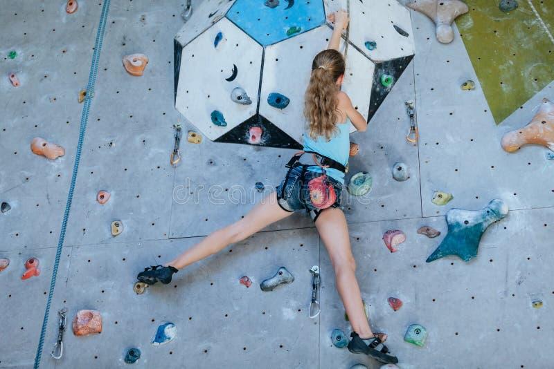 One teenager climbing a rock wall indoor. stock photo