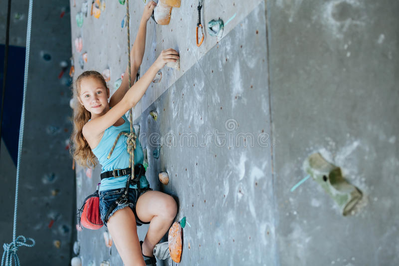 One teenager climbing a rock wall indoor. royalty free stock photography