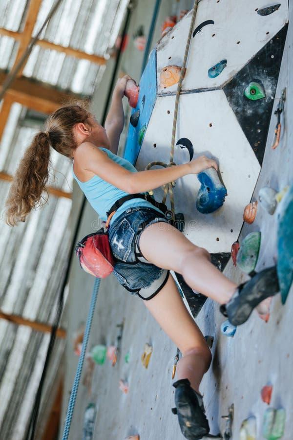 One teenager climbing a rock wall indoor. royalty free stock photos