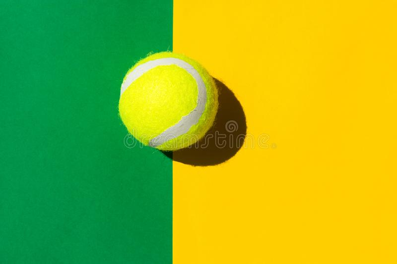 One tennis ball on duotone yellow green court background in bright sunlight sports active lifestyle competition victory. Concentration concept. Creative royalty free stock photos