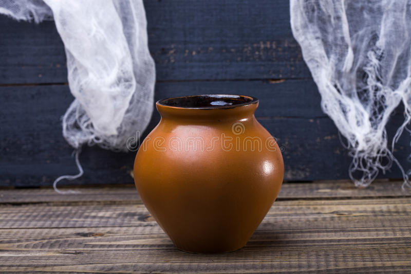 One terra-cotta brown clay pot. Photo still life closeup one whole terra-cotta brown clay pot standing on wooden table over blue rustic background, horizontal royalty free stock image