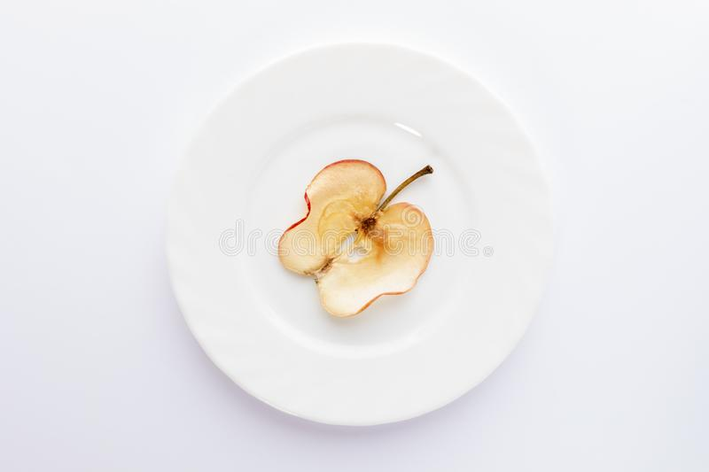 One thin slice of dried apple on round white plate on white background royalty free stock image