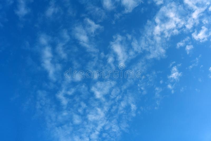 One-time blue fluffy clouds completely tightened all sky over the sea the sun is not visible yet, it behind the horizon, but beams stock image
