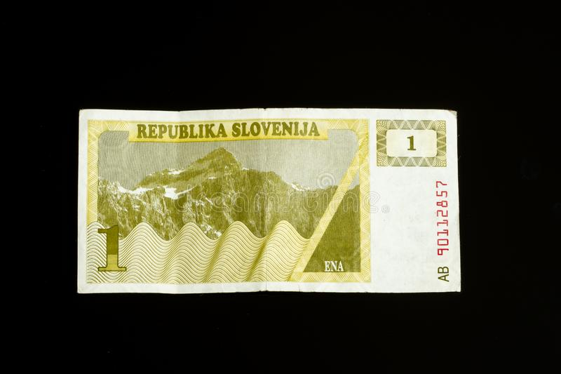 One 1 tolar bill of Slovenia, first paper bank note introduced after declaring independance. Isolated on black stock photos
