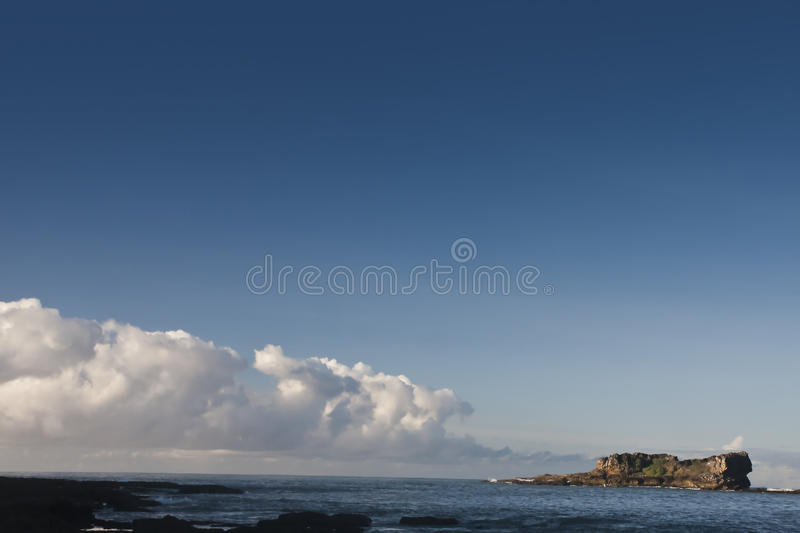 Big Stone at Sea in the morning. One of the top destination located on Banten, Indonesia. This photograph is about iconic big stone with marvelous cloud and blue royalty free stock photography