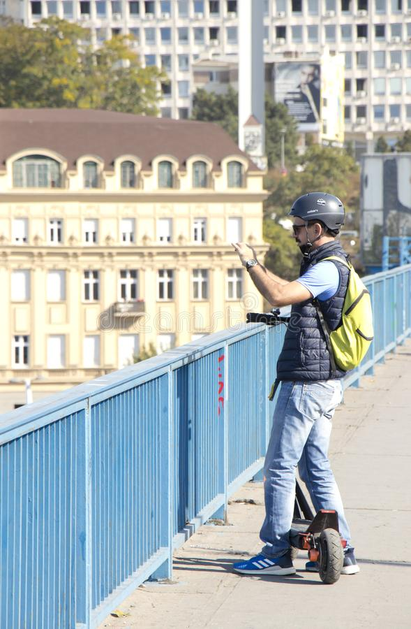 One tourist man sightseeing while riding an electric scooter on city street bridge sidewalk royalty free stock photo